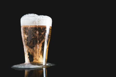 foam beer poured from a glass on a black background with copy space