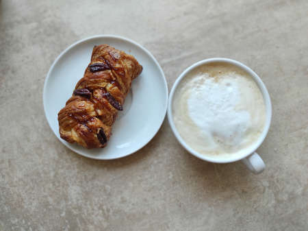 Cappuccino in a white cup with maple pecan on a saucer