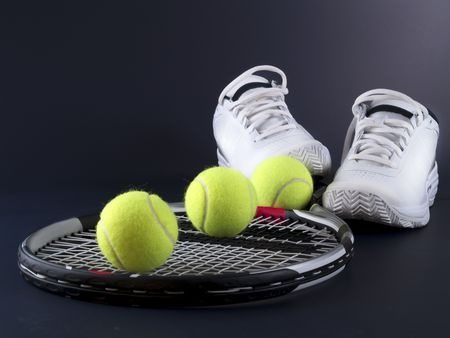 tennis shoe: tennis racket, three balls and shoes on black