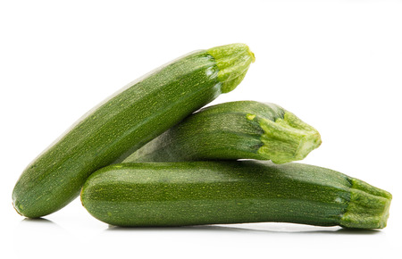 three green and fresh zucchini on white background