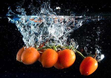 une grappe de tomates tombant dans l'eau