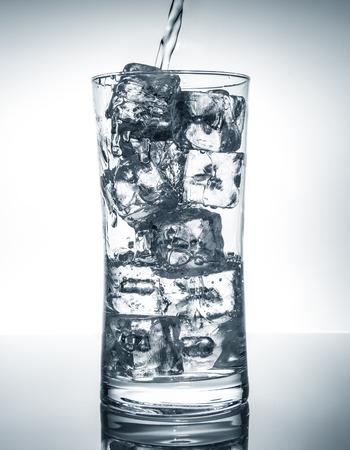 agua dulce que fluye en un vaso con hielo