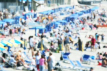 crowded beach background with unrecognizable people with intentional blur effect