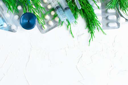 Christmas medical flatlay. On a white background. Syringes, stethoscope, blood test tube, coronavirus vaccine, pills others equipment of doctor. FlatLy medicine new year xmas. Copyspace