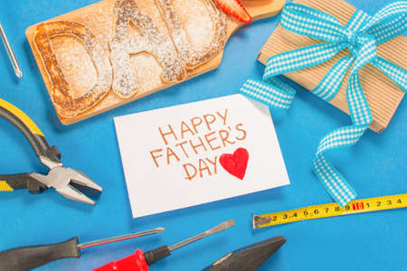 Childs drawing of her dad. Father day Breakfast pancakes DAD letters, gift, building tools on a blue background. Concept Happy Fathers Day flat lay