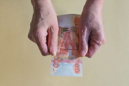 Senior woman counts one five thousand banknote of rubles bills. Hands and money of the old woman. Old age, pension, retirement saving concept