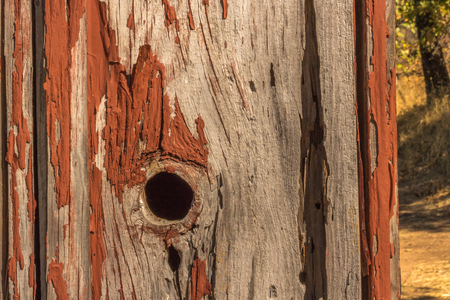 Detail of peeling red paint on aged wood for background