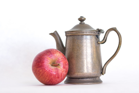 Retro pewter antique, silver color old fashioned teapot with a homegrown red delicious apple next to it on a white background