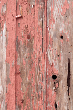 Detail of old, peeling red paint on small, wood out building background
