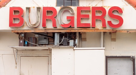 Retro red burger sign from the 60s in disrepair, rusty gray electrical boxes and conduit below sign, white background