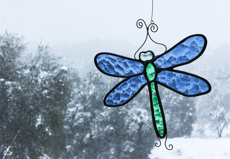 Cold snow day with oak trees seen through a window with bright blue and green stained-glass dragonfly sun catcher hanging in window