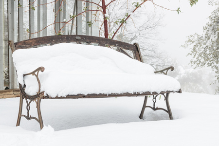 Snow covered empty vintage old garden bench on a col wet misty snowy day Standard-Bild - 110518979