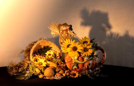 Centrotavola cornucopia del Ringraziamento con brocca di zucca in porcellana, girasoli e spaventapasseri che celebrano le vacanze autunnali del raccolto autunnale, simboli stagionali di abbondanza e abbondanza