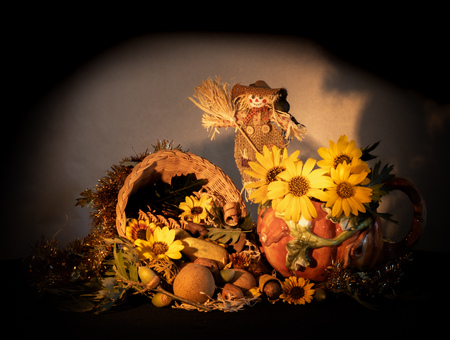 Thanksgiving cornucopia centerpiece with porcelain pumpkin pitcher, scarecrow, sunflowers and oak leaves celebrating fall autumn harvest holiday, seasonal symbols of plenty and abundance isolated with soft black vignette