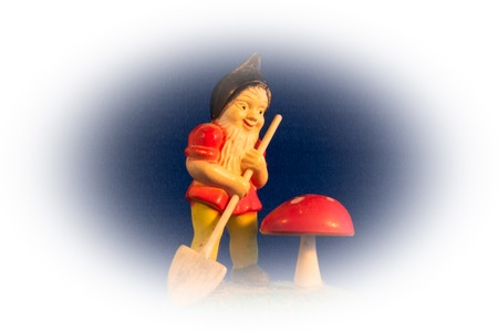 Close-up of miniature vintage gardening gnome with a small shovel and red poison toadstool, mushroom Stock Photo