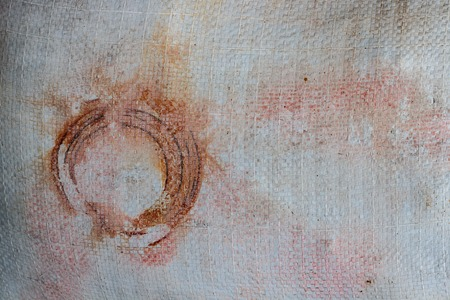 Old white tarp with circular rust, stains, a gunge vintage look in shades of red, orange color, brown and gray