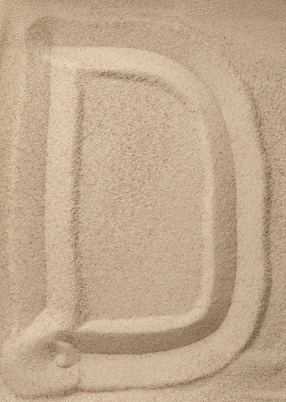 Letter D of the alphabet writing on the sand photo