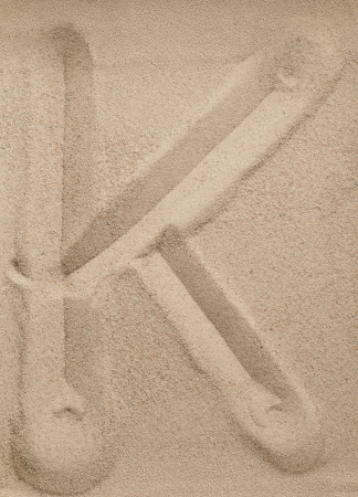 Letter K of the alphabet writing on the sand photo