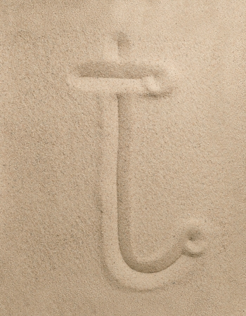 Letter t of the alphabet writing on the sand photo