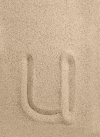 Letter u of the alphabet writing on the sand photo