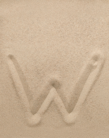 Letter w of the alphabet writing on the sand photo