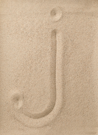 Letter j of the alphabet writing on the sand photo