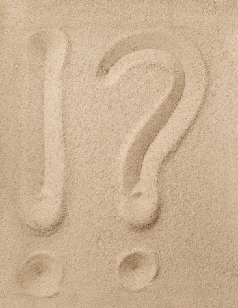 Exclamation point and question mark writing on the sand photo