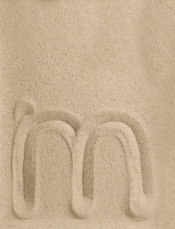 Letter m of the alphabet writing on the sand photo