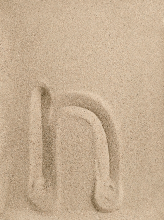 Letter n of the alphabet writing on the sand photo