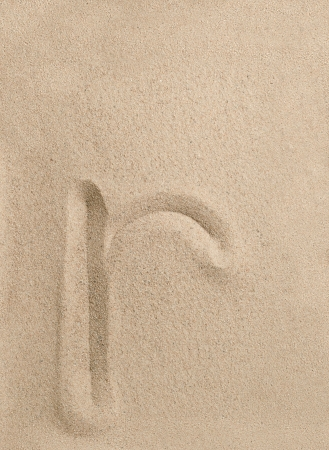 Letter r of the alphabet writing on the sand photo
