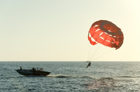 parasailing: Parasailing on a red parachute over water Stock Photo