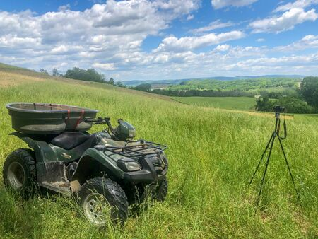 Off road vehicle and camera tripod atop grassy agricultural field with blue sky background and copy space.