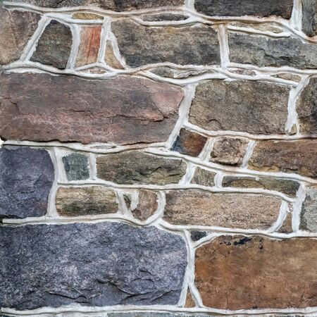 Colorful fieldstone masonry wall shows artistic strength and heft. Old fashioned mortar work with stones of varying shapes and sizes. Natural light and color, graceful lines, patterns, with copy space Imagens