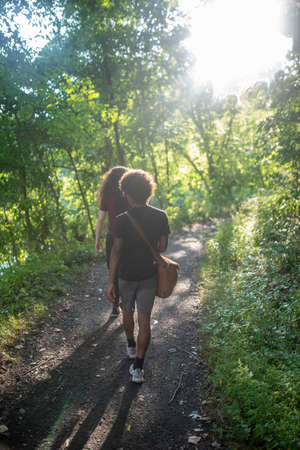 Young African American and Caucasian men hike forest trail.