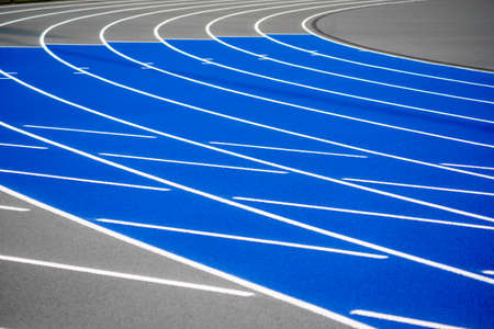 Curved blue and gray running track with textured surface, crisp lines