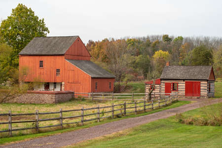 Red barn and log cabin on dirt road at historic Daniel Boone Homestead