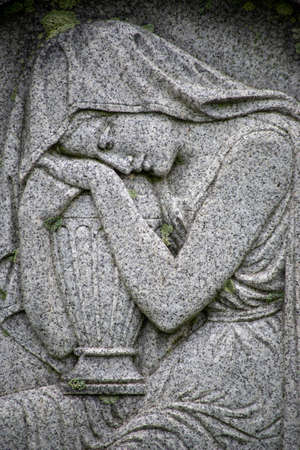 Woman on a Victorian tombstone embraces an urn 版權商用圖片