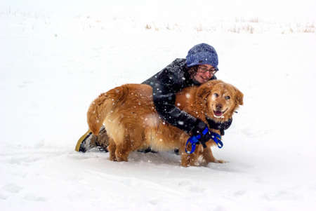 Young woman embraces her happy dog in the falling snow