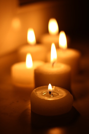funeral background: Holiday candles burning on a white background and reflected Stock Photo
