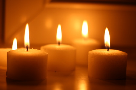 Holiday candles burning on a white background and reflected 版權商用圖片