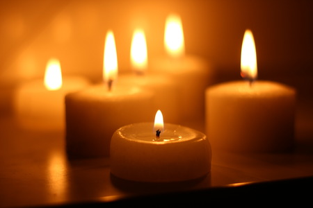 candlelight: Holiday candles burning on a white background and reflected Stock Photo