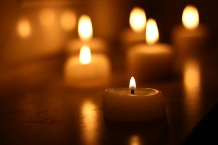 Vakantie kaarsen branden op een witte achtergrond en gereflecteerd Stockfoto