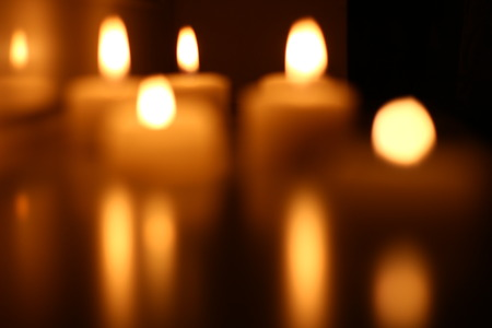 Holiday candles burning on a white background and reflected Stockfoto