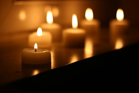 christmas memories: Holiday candles burning on a white background and reflected Stock Photo