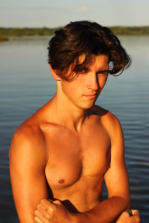 aqua naked: Handsome fit shirtless young man with long black hair posing demonstrates biceps muscles next to water pond or river, looking at camera.