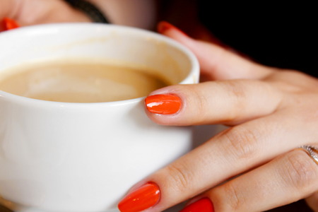 crema: woman holding hot cup of coffee, with heart shape.