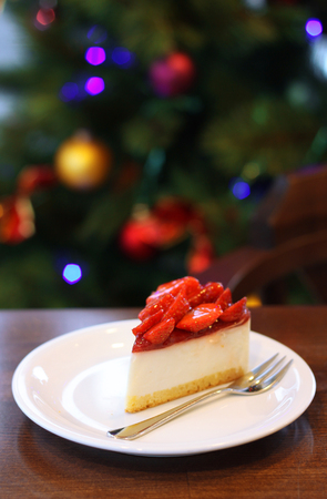 a portion: Fresh strawberry cheesecake. Selective Focus on the front upper edge of cake. Christmas tree in background.