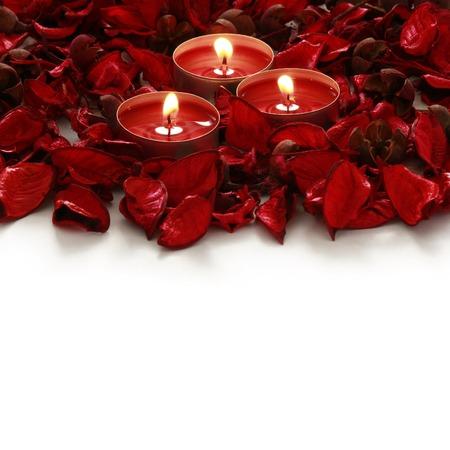 赤いバラとテキストのスペースと白い背景の上のろうそく 写真素材