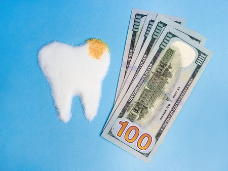 Tooth from white and bown sugar with money on blue background, symbol Standard-Bild