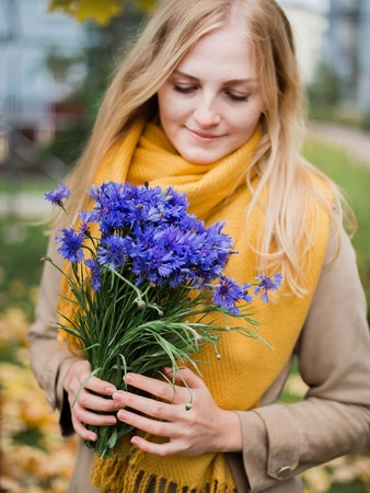 Woman with flowers, cornflower bouquet on female hand